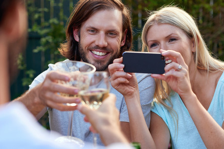 group of friends drinking cheers taking picture photos on mobile cellphone camera at outdoor garden party photo