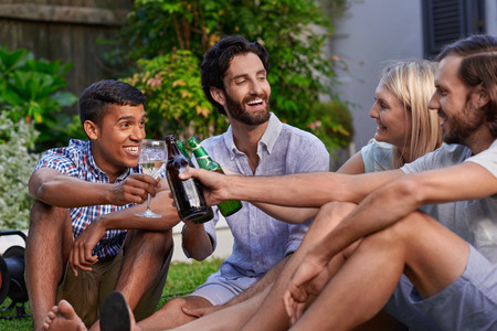 diverse group of friends having outdoor garden party with beer and wine drinks