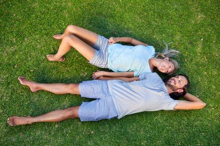 personas abrazadas: Pareja relajada joven feliz en el amor que se establecen en la sobrecarga de hierba Foto de archivo