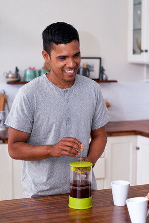 morning routine: man preparing french press plunger coffee for early morning routine in kitchen