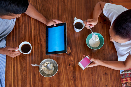 couple enjoying a healthy morning breakfast cereal with tablet computer and mobile phone in kitchen at home photo