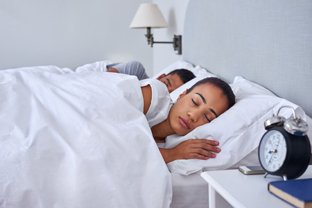 calmness: peaceful young couple sleeping comfortably in bed at home Stock Photo