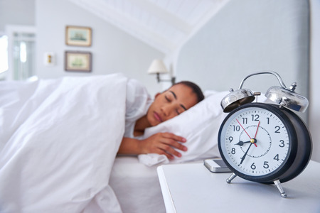 morning routine: alarm clock young woman sleeping comfortably in bed at home Stock Photo