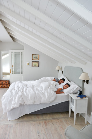 bed: peaceful young couple sleeping comfortably in bed at home Stock Photo