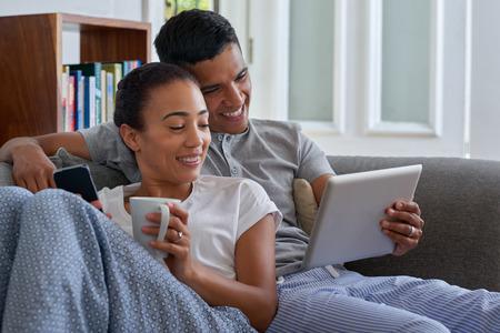 Sorridente coppia con il computer tablet sul divano divano a casa Archivio Fotografico - 39227197