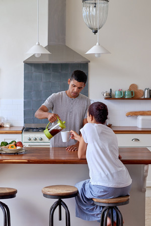 mixed couple: husband is pouring coffee for his wife in kitchen early morning breakfast routine