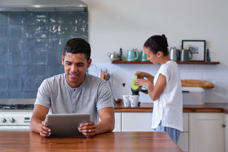 tablet: man sitting with tablet computer in kitchen at home while wife makes morning coffee Stock Photo