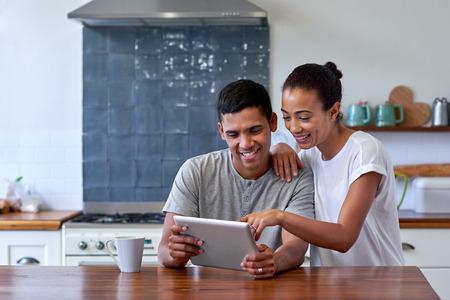 parejas jovenes: pareja de unión y disfrutando de café de la mañana con el ordenador tableta en la cocina en el hogar Foto de archivo