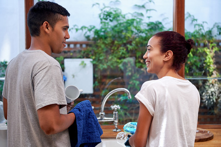 husband and wife: young woman washing dirty dishes while husband dry off in kitchen