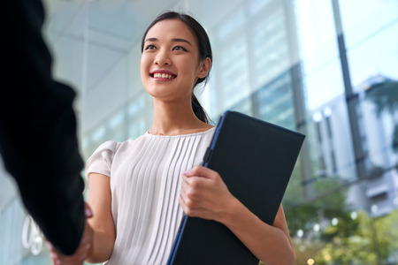 stretta mano: Bella donna asiatica di affari cinese che agita le mani in città moderna ufficio lavoro