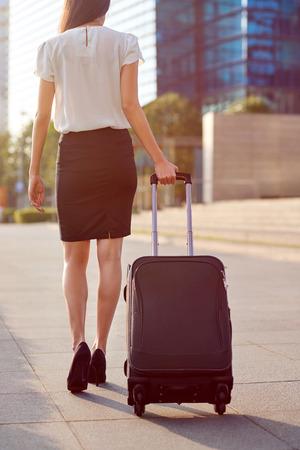travel bag: travel business woman pulling suitcase bag walking along sidewalk outdoors in urban city