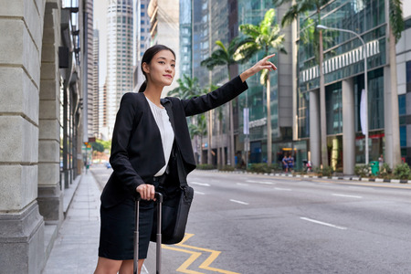 traveling asian chinese business woman calling for taxi cab from city street sidewalk Banque d'images