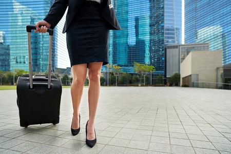 femme valise: femme d'affaires de Voyage tirant sac valise marche sur le trottoir à l'extérieur dans la ville urbaine