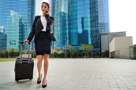アジア中国語旅行携帯電話屋外都市で歩道に沿って歩いてスーツケース バッグを引っ張るビジネス女性