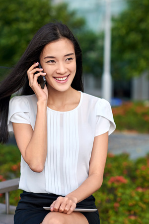 windy city: asian chinese businesswoman office worker communicating with mobile phone on coffee break outdoors Stock Photo