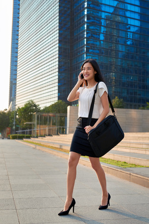 asian chinese businesswoman office worker in downtown business district on sidewalk with mobile phone