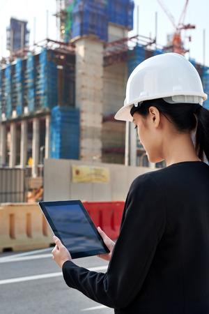 trabajando duro: profesional de emplazamiento de la obra supervisando mujer de negocios con la protecci�n del sombrero duro en el trabajo