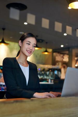若いアジアの中国ビジネス女性ラップトップ コンピューター仕事のためカフェ wifi 接続を使用して