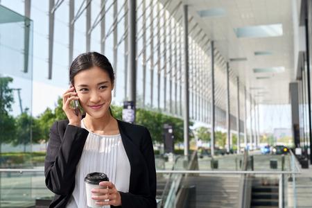 アジア中国実業家オフィス ワーカーのコーヒー ブレークに携帯電話との通信 写真素材