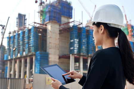 professional business woman supervising construction site with hard hat protection at work