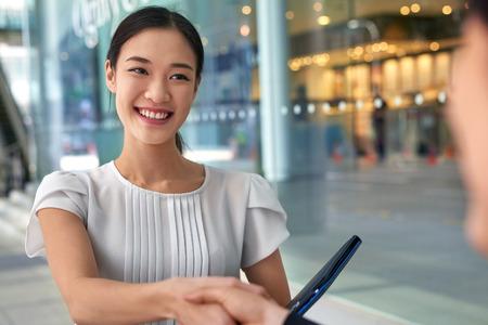 dando la mano: hermoso de la mujer de negocios chino que sacuden las manos en ciudad moderna oficina de trabajo Foto de archivo