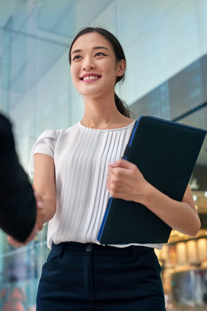 welcome smile: beautiful asian chinese business woman shaking hands in modern city work office