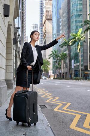 cab: viajar asi�tico mujer de negocios chino pidiendo taxi desde la ciudad acera calle