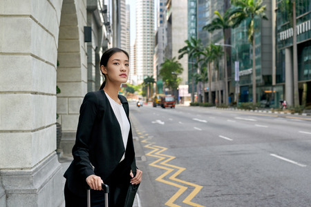sidewalk: traveling asian chinese business woman waiting for taxi cab along city street sidewalk Stock Photo