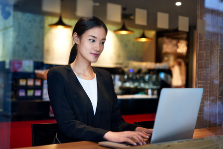 laptop asian: young asian chinese business woman using cafe wifi connection for laptop computer work
