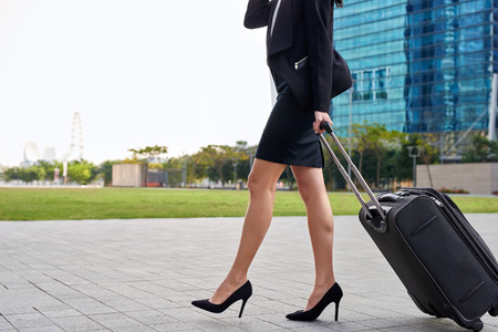 piernas con tacones: mujer de negocios de viajes tirando bolsa maleta caminando a lo largo de la acera al aire libre en la ciudad urbana moderna
