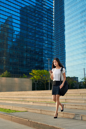 asian businesswoman: asian chinese businesswoman office worker in downtown business district on sidewalk with mobile phone