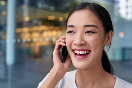 hablando por telefono: happy asian chinese business woman talking on mobile cell phone at work