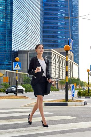 Aziatische Chinese zakenvrouw kruising straat lopen om te werken met koffie drinken en tas in de stedelijke wijk