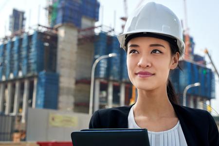 専門的なアジアの中国ビジネス女性職場のハード帽子の保護で工事現場の監督