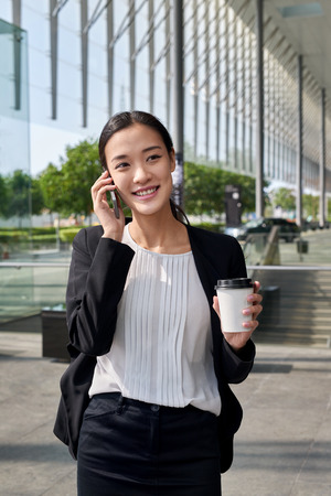 asian chinese businesswoman office worker communicating with mobile phone on coffee break photo