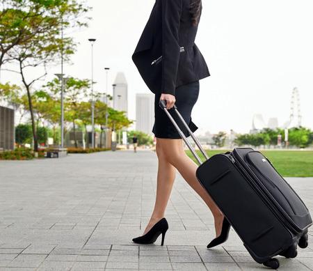travel bag: travel business woman pulling suitcase bag walking along sidewalk outdoors in modern urban city