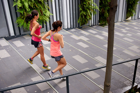 run down: sporty women running down stairs outdoors for morning workout Stock Photo
