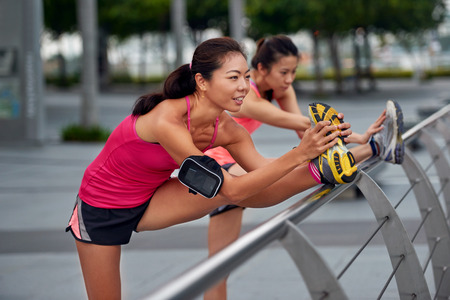 warm up: athletic asian chinese women doing stretching exercises outdoors along city sidewalk