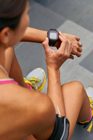 heart monitor: woman sitting outdoors checking workout time on wearable technology watch after run
