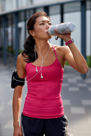 quenching: asian chinese sporty woman outdoors quenching her thirst with water bottle during morning workout Stock Photo