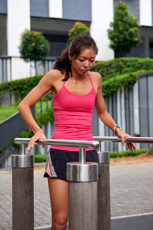 outdoor fitness: athletic fitness asian chinese woman working out on outdoor park gym
