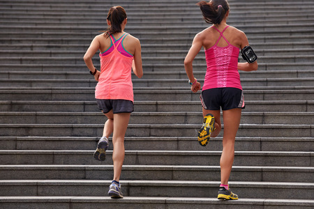 woman stairs: active sporty women working out running up stairs outdoors for morning workout Stock Photo
