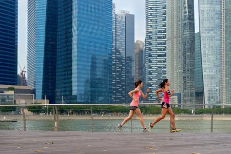 sidewalk: sporty women working out running outdoors along urban city harbor sidewalk morning