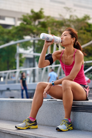 sporty asian chinese woman sitting outdoors resting drinking water bottle after morning run