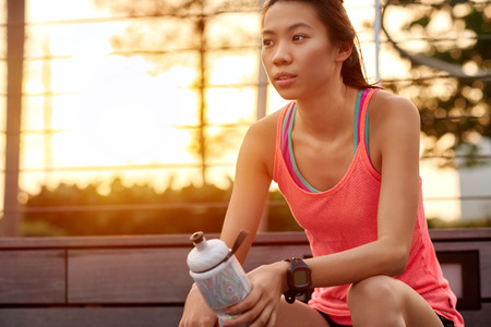 thinking woman: sporty asian chinese woman sitting outdoors resting with water bottle after morning run