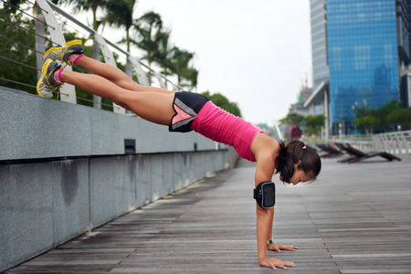 legs: active strong woman doing pushup strengthening workout along outdoor city sidewalk with elevated legs