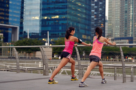 active sporty women stretching exercise outdoors along city sidewalk Banque d'images