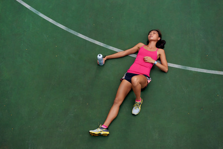 passed out: exhausted sporty woman runner laying on basketball court after fitness running workout outdoors Stock Photo