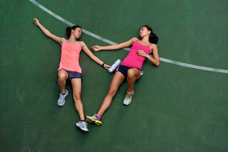 overheating: exhausted sporty women runners laying on basketball court after fitness running workout outdoors
