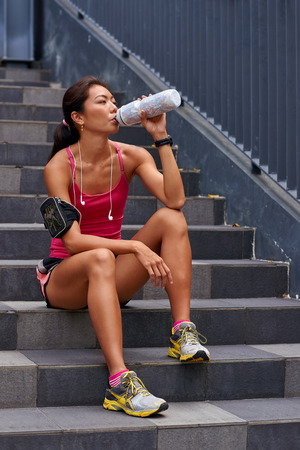 dehydrated: asian chinese sporty woman sitting on steps outdoors quenching her thirst with water bottle after morning workout